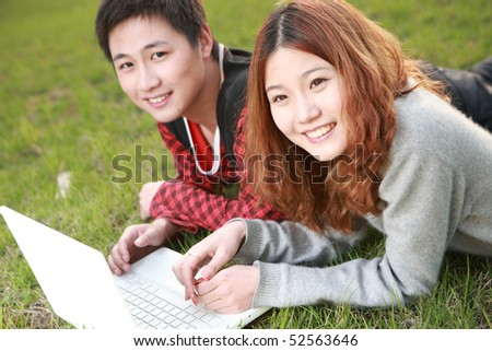 couple of young useing laptop