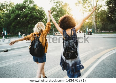 Couple of young women from the back holding hands with arms raised and walking in the street at sunset - Two millennials have fun