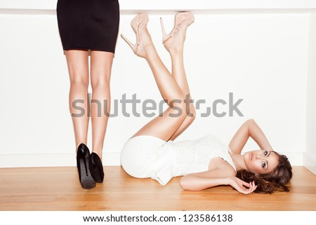 couple of young women in elegant dresses and high heel shoes indoor shot