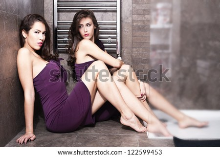 couple of young women in elegant dresses in bathroom