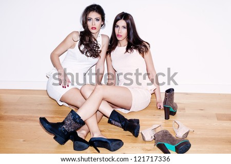 couple of young women with lots of shoes on the floor