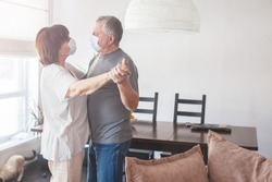Couple old aged senior people at home with seasonal winter cold illness disease dancing at kitchen. Elderly couple in medical masks during the pandemic Coronavirus CoVid-19