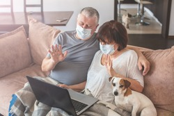 Couple old aged senior people at home with seasonal winter cold illness talking skype sit down on the sofa. Elderly couple in medical masks during the pandemic Coronavirus CoVid-19