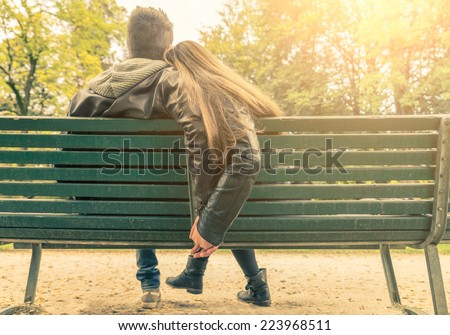 Couple on a bench - Two lovers sitting on a bench in a park and holding themselves by hands - Concepts of autumn,love,togethe rness,relationship