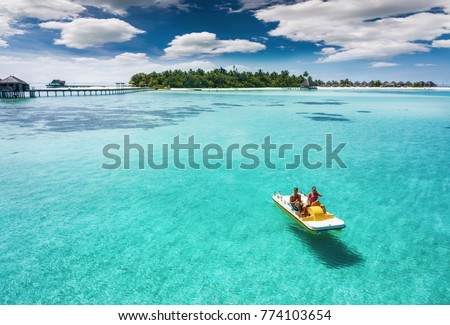 Stock Photo Couple on a pedalo boat is enjoying the turquoise waters of the tropical Maldives