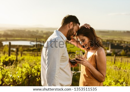 Couple on a romantic date standing together drinking red wine in a wine farm. Couple on a wine date spending time together.