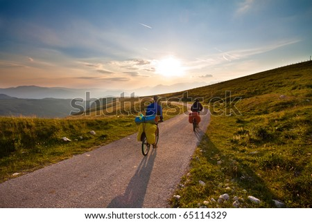 Couple on bicycles on mountain road