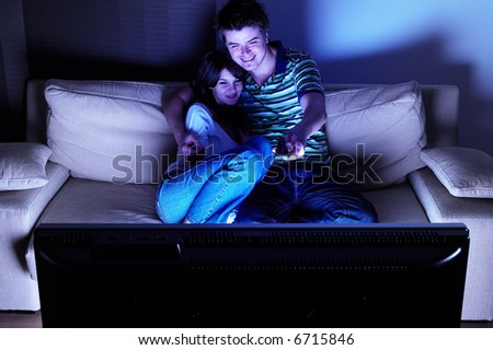 Couple on couch watching TV - having a great time