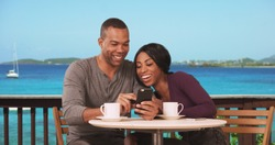 Couple on honeymoon sitting at restaurant with ocean view drinking coffee