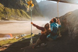 Couple on swing having fun outdoor travel vacations lifestyle friends man and woman together enjoying mountains view in Norway summer journey