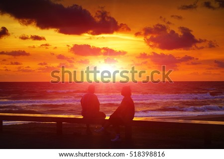 couple on the beach at colorful sunrise on background.