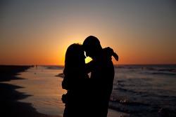 Couple on the beach at sunrise