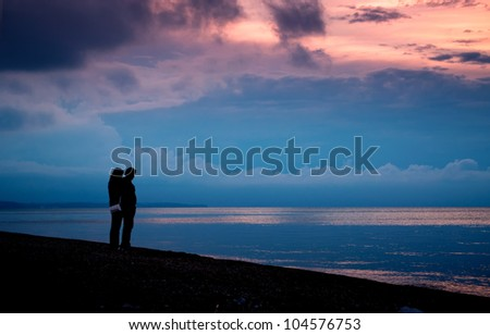 Couple on the beach at sunset and stormy clouds over the sea