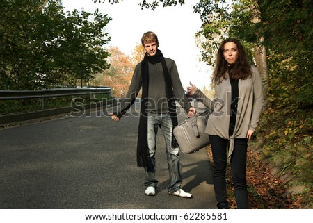 couple on the road waiting for a car - stock photo