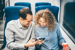 Couple on train using smart phone and smile.