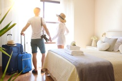Couple on vacation with suitcases holding hands on their backs looking out a window in a bright hotel room.