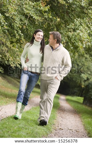 Couple on walk along woodland path in autumn