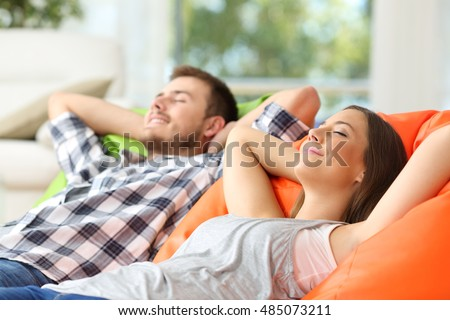 Couple or roommates relaxing lying on comfortable poufs in the living room at home