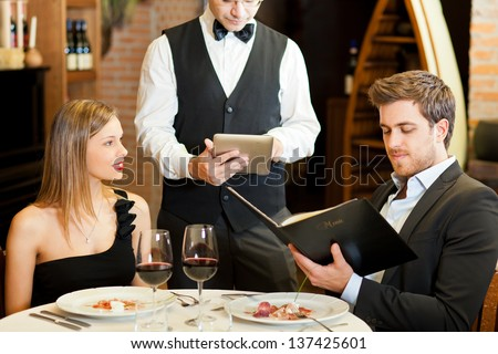Couple ordering meal at restaurant