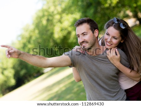 Couple outdoors looking at something and pointing with the hand