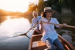 Couple paddling canoe on the sunset lake