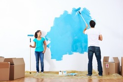 couple painting new home together with blue color happy and carefree relationship