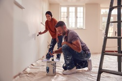 Couple Painting Test Squares On Wall As They Decorate Room In New Home Together