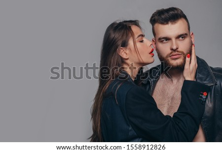 Couple passionate people in love. Passion fashion. Man brutal well groomed macho and attractive feminine girl long hair cuddling. Girlfriend passionate red lips and man leather jacket. Passionate hug.
