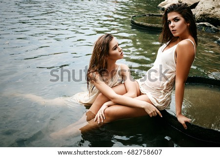 Couple passionate sexual female girls, dressed in a light dressing gown, show love, swimming and sitting in the river wet and very beautiful