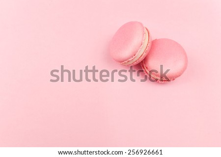 Couple pink macaroons lying on pink background