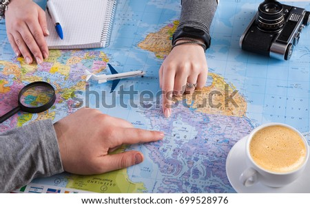 Couple planning airplane trip to Canada, point on map, taking notes in blank notebook, copy space - Shutterstock ID 699528976