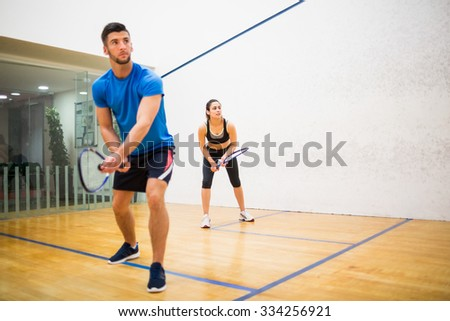 Couple play some squash together in the squash court ストックフォト ©