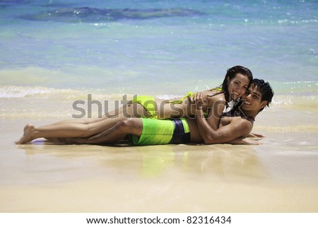 couple playing at the water's edge on a hawaii beach