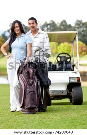 Couple playing golf posing with a cart and a bag smiling