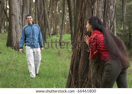 Couple playing hide and seek in forest