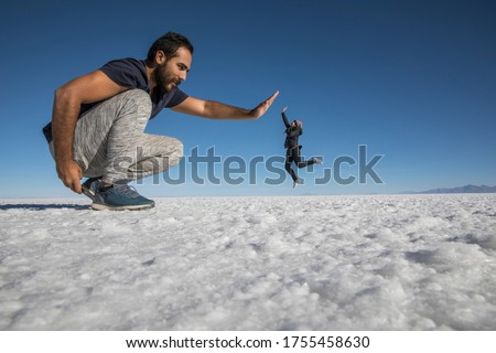 Couple playing in the desert salt flats, having fun with perspective Сток-фото ©