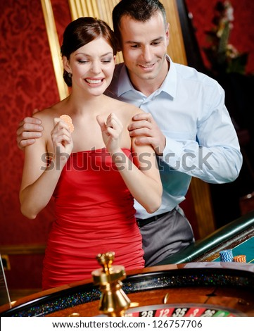 Couple playing roulette follows the game at the casino
