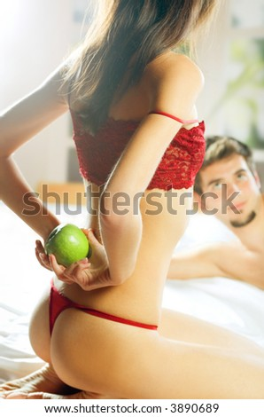 Couple playing with apple on the bed in bedroom. Focus on woman with apple.