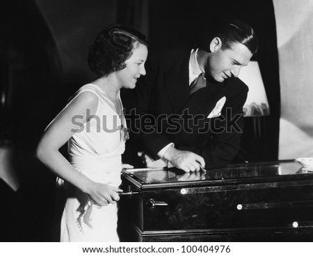 Couple playing with pinball machine