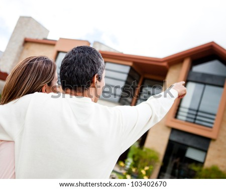 Couple pointing at their lovely dream home