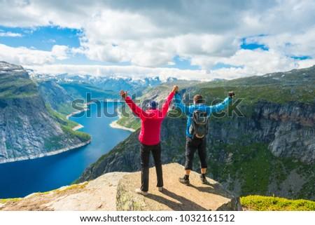 Couple posing on Trolltunga. Happy woman and man enjoy beautiful lake and good weather in Norway. #1032161512