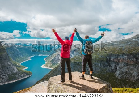 Couple posing on Trolltunga. Happy woman and man enjoy beautiful lake and good weather in Norway. #1446223166