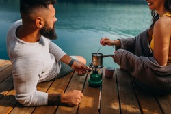 Couple preparing fresh coffee while sitting on a pier