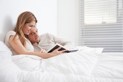 couple reading a book lying in the bed