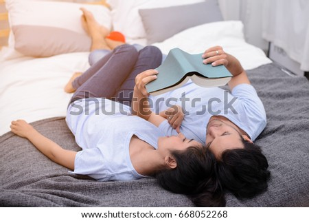 Couple reading a book together in bedroom. #668052268