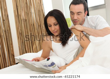 Couple reading a magazine on the bed