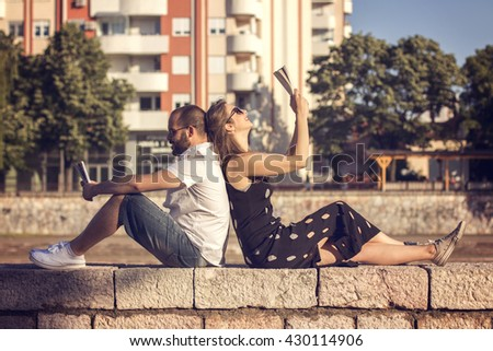 Couple reading books by the river on sunny day