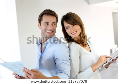 Couple reading news on newspaper and internet