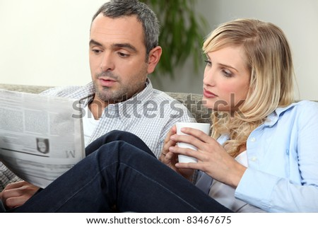 Couple reading newspaper on couch
