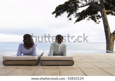 Couple reclining on sun beds by infinity pool, looking at sea, back view